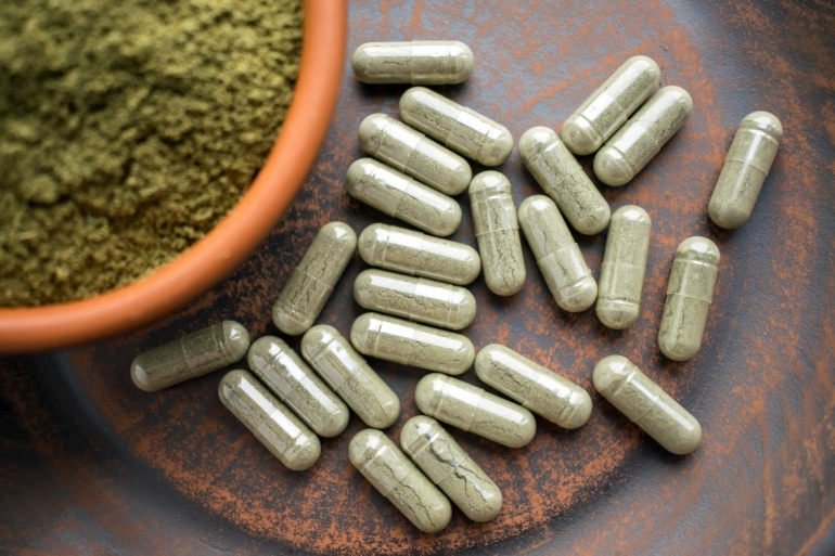 supplement-kratom-green-capsules-and-powder-on-brown-plate-herbal-product-alt-medicine-kratom